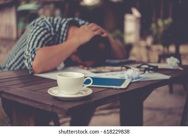 Depressed Businessman Leaning His Head Below when not success work. focus focus a cup of coffee. collapse concept, Vintage style.
