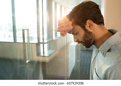 Depressed businessman leaning on glass at office