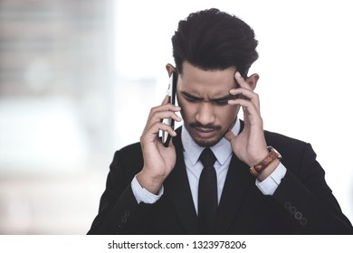 Depressed businessman looking at his smartphone with bad news about his financeial crisis