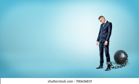 A depressed businessman on blue background stands with a lowered head while chained to an iron ball. Business world restrictions. Credit burden. Financial obligations.