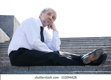Depressed businessman. Sad senior man in formalwear sitting on stairs and holding his hand on chin