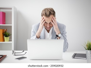 Depressed businessman sitting at computer