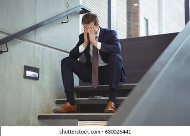 Depressed businessman sitting on stairs at office