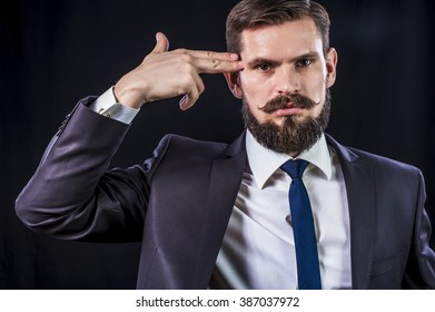 Depressed businessman in suit with finger's gun near the head