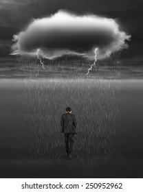 Depressed businessman walking with dark cloud of rain and lightning over his head