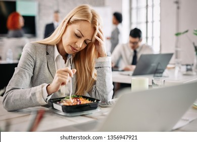 Depressed businesswoman holding her head in pain while having vegetable salad for lunch in the office.