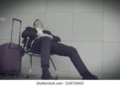 Depressed caucasian businessman traveler and business trip waiting flight in the terminal with luggage at airport after flight delay and cancellation. Desperate passenger flight delay concept, toned