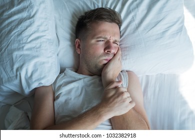 Depressed caucasian ill man in white t'shirt having toothache and touching cheek. He is in bed at home