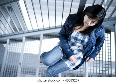 Depressed chinese girl in metal stairs