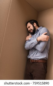 depressed crying man and huging himself in cardboard box