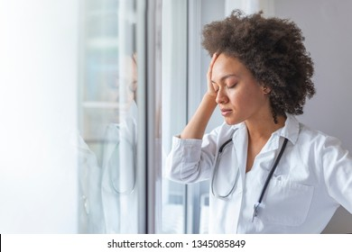 Depressed doctor. Tired doctor near window. Closeup portrait sad health care professional with headache, stressed, holding head against window glass.