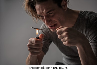 Depressed drug addicted male person preparing a spoonful of opiate. Isolated on background