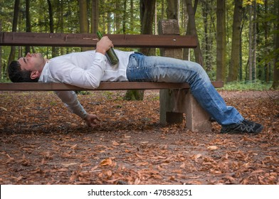 Depressed drunk man asleep outdoor on a park bench with beer bottles