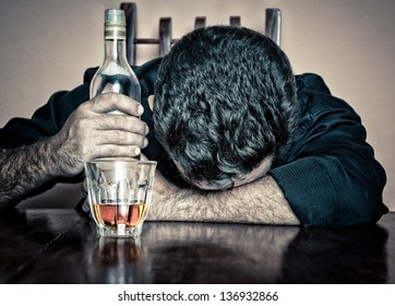 Depressed  drunk man with a glass and a bottle sleeping with his head on a table