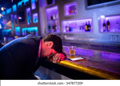 Depressed drunk man sleeping with his head on the table in bar