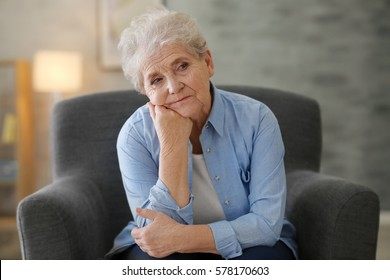 Depressed elderly woman sitting in arm-char at home