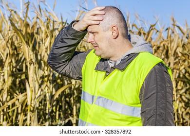 Depressed farmer on cold corn field