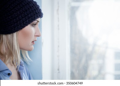 Depressed female druggie wants a new done. The woman is standing and looking through the window with disappointment. Copy space in right side