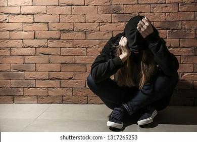 Depressed female junkie near brick wall. Concept of addiction