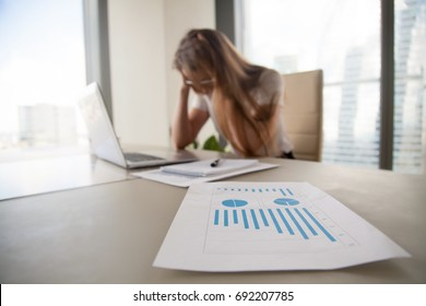 Depressed frustrated businesswoman holding head in hands, female boss shocked by decreasing sales in documents, focus on falling stats, profit loss graphs, company bankruptcy or financial problems