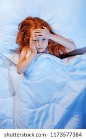 Depressed girl in bed having headache