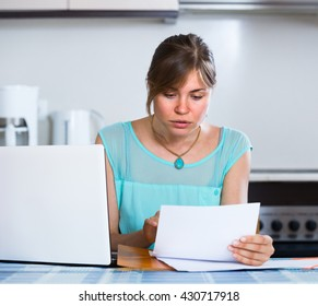 Depressed girl at kitchen receiving bank refuse about delay of payment