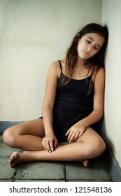 Depressed girl with a sad expression sitting in a corner