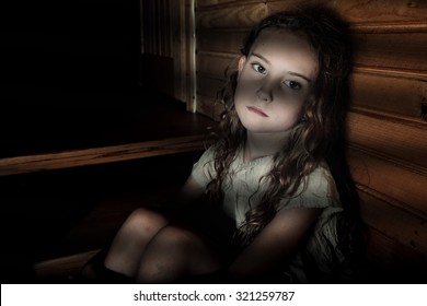Depressed girl sitting in a dark hallway in home