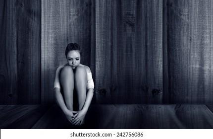 depressed girl sitting near the wall