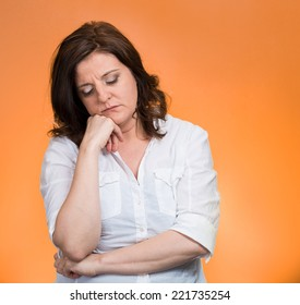 Depressed, gloomy. Closeup portrait unhappy middle age woman head on hand bothered by mistake situation having bad headache isolated orange background. Negative human emotion facial expression feeling