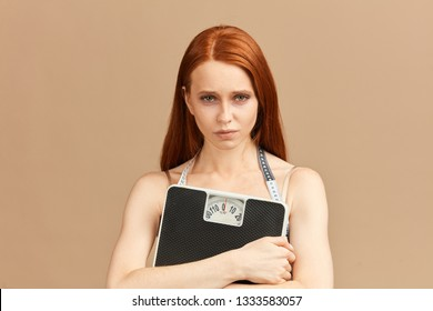 Depressed gloomy woman feeling pressure and stress about weight loss, diet or gaining weight. Eating disorder, anorexia or bulimia concept.