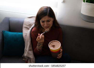 Depressed and heartbroken young latin woman eating chocolate ice cream while crying on the sofa. Hispanic woman feeling lonely