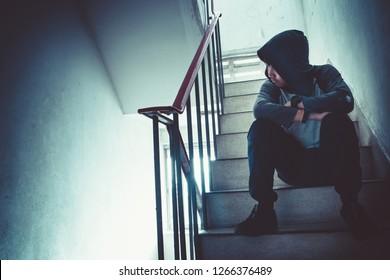Depressed Hooded man sitting on the footbridge, Sad man, Cry, drama concept - Image