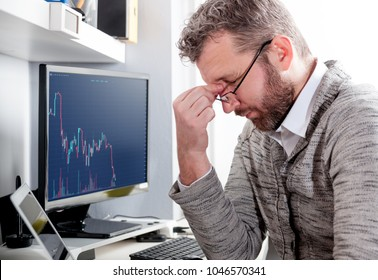 Depressed investor analyzing crisis stock market with charts on laptop screen at home office