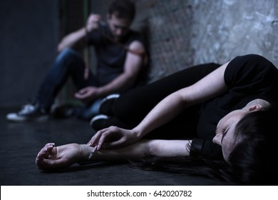 Depressed junkies getting drug injection on the ground