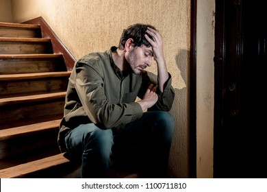 depressed latin man sitting head in hands inside in a stairwell feeling lonely and sad and stressed about work and life in a mental health concept