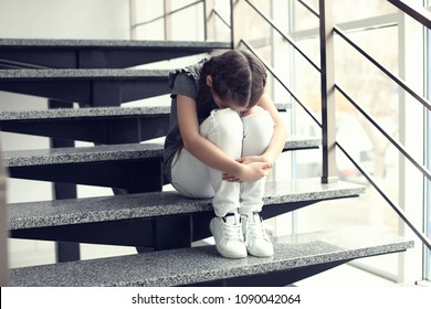 Depressed little girl sitting on stairs indoors. Time to visit child psychologist