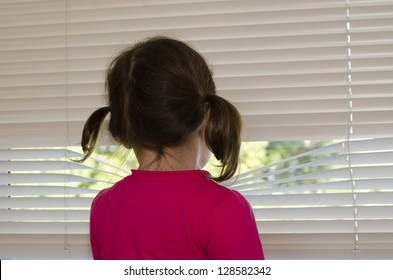 Depressed, lonely and abused little girl looks outside through window.