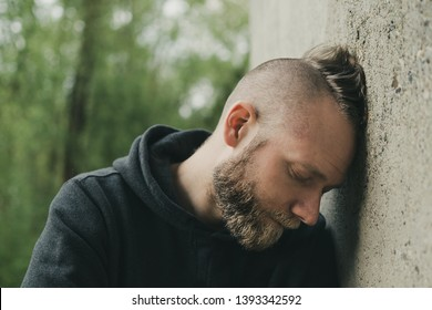 depressed and lonely man his head against a wall