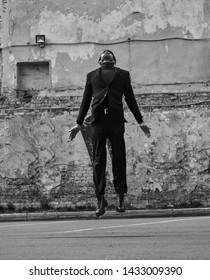 Depressed lonely man jumping and wanting to fly and travel from problem. Business concept of free. Outdoor portrait. Black and white