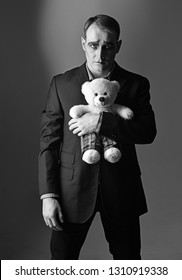 Depressed and lonely. Mime man hold teddy bear toy. Stage actor with mime makeup in toy shop. Theatre actor miming sad emotions. Unhappy mime artist. Theatrical performance art and pantomime drama.