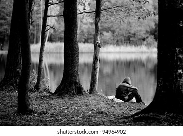 A depressed, lonely person wearing a hood is sitting near the lake