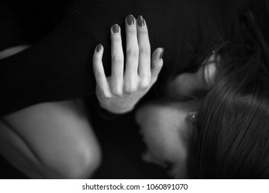 Depressed lonely woman laying on sofa and hug self. Black and white photo