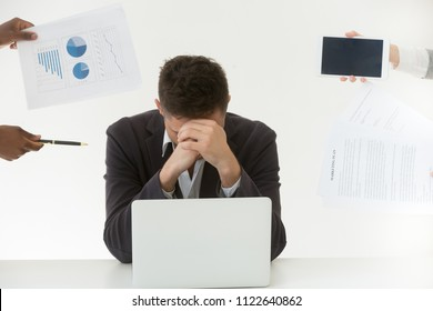 Depressed male employee in despair exhausted by excessive workload and annoying colleagues, tired worker feeling fatigue suffering from work stress and headache trying to control emotions.
