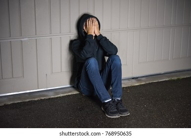 Depressed male teenager sitting on ground in front of garage door and covering his face.