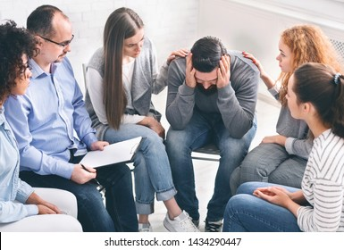 Depressed man with alcoholism problem sitting in rehab center, group supporting him, free space