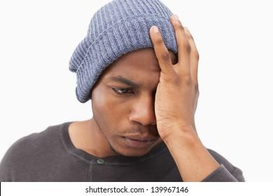 Depressed man in beanie hat on white background