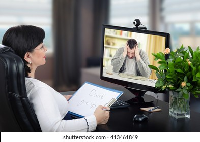 Depressed man is exceedingly despondent at first encounter with virtual psychotherapist.  Man sits with his head in his hands. Black-haired glasses psychotherapist watches and listens him on monitor.
