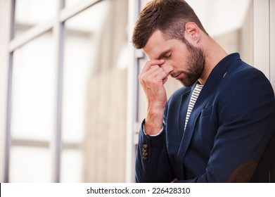 Depressed man. Frustrated young man in smart casual wear touching his face with hand and keeping eyes closed while standing indoors