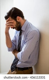Depressed man with hand on forehead at home